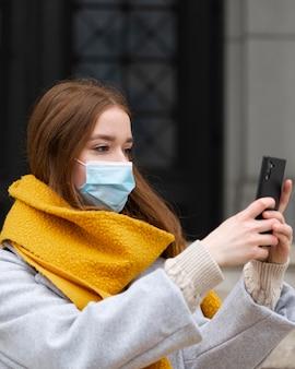 スマートフォンで写真を撮る医療マスクを持つ女性の側面図