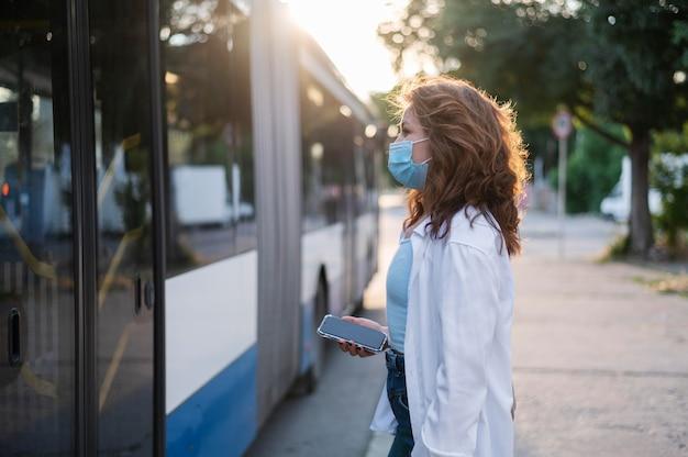 공공 버스가 문을 열기를 기다리는 의료 마스크를 쓴 여성의 측면