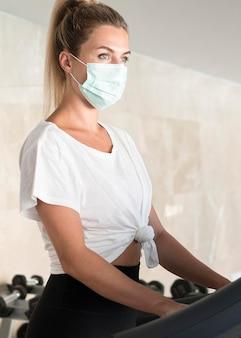 Вид сбоку женщины с медицинской маской, тренирующейся в тренажерном зале