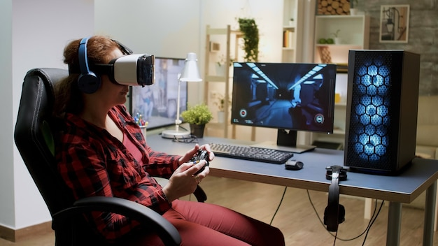 ワイヤレスコントローラーでビデオゲームをプレイしながら、vrゴーグルを身に着けている赤い髪の女性の側面図。
