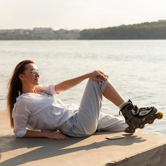 湖のほとりで太陽の下でポーズをとってローラーブレードを持つ女性の側面図