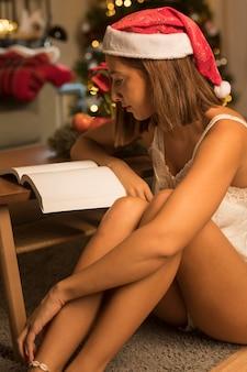 クリスマスに本を読んでサンタの帽子をかぶった女性の側面図