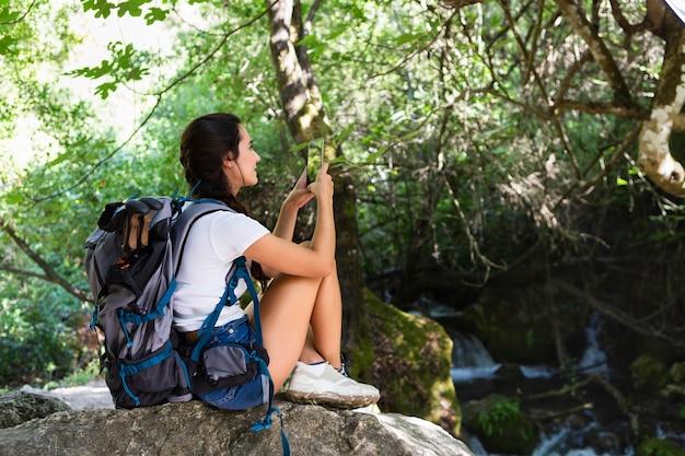 Вид сбоку женщины со смартфоном на природе