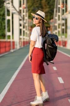 Вид сбоку женщины в солнцезащитных очках и шляпе, путешествующей в одиночку