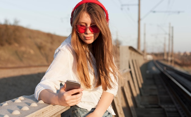 Вид сбоку женщины с солнцезащитные очки и наушники, держа смартфон