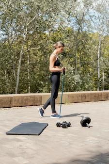 屋外でトレーニング機器を持つ女性の側面図