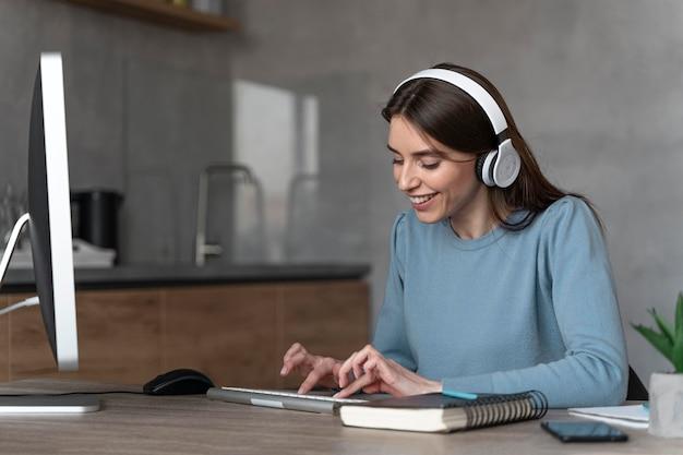 コンピューターとヘッドフォンでメディア分野で働く女性の側面図