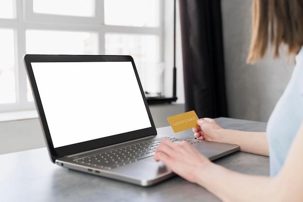 Вид сбоку женщины работают на ноутбуке и проведение кредитной карты