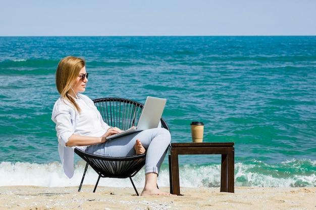 ビーチでラップトップに取り組んでいる女性の側面図