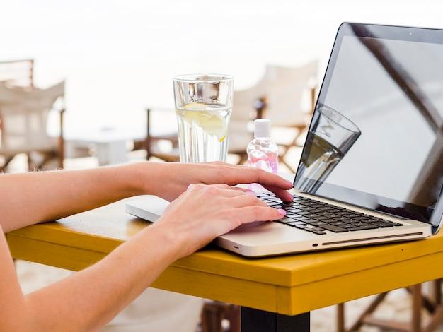 Взгляд со стороны женщины работая на компьтер-книжке снаружи