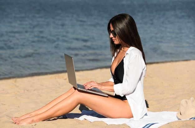 Вид сбоку женщины, работающей на пляже с ноутбуком