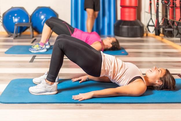 ジムでトレーナーと骨盤運動をしている女性の側面図。ジムのコンセプト。