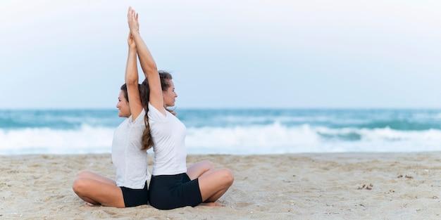 Вид сбоку женщин, практикующих йогу на пляже