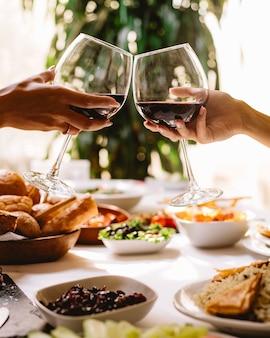 レストランで赤ワインのグラスで乾杯する女性の側面図