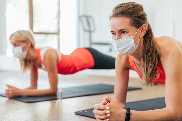 Вид сбоку на женщин с медицинскими масками, тренирующихся вместе