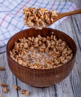 Вид сбоку деревянной ложкой и миску с воздушным сладким рисом на деревенском