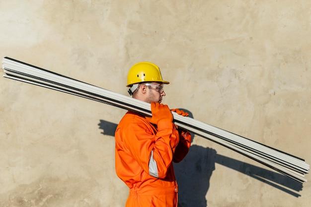 Вид сбоку на работника в защитных очках и каске, несущей сталь