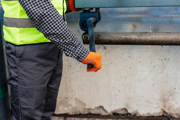 Вид сбоку на работника в защитных перчатках и светоотражающем жилете