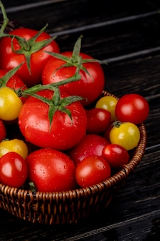 木のバスケットに黄色と赤のトマトの側面図