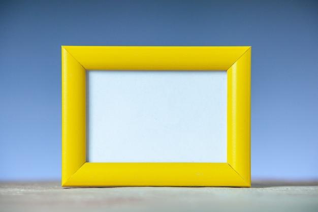 Вид сбоку желтой пустой фоторамки, стоящей на белом столе на поверхности синей волны со свободным пространством