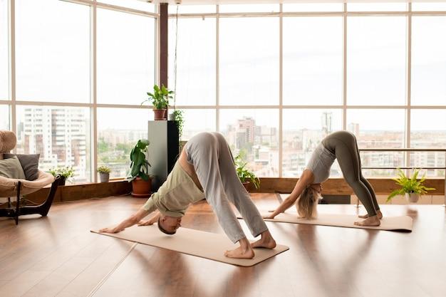 Вид сбоку молодой активной пары в спортивной одежде, наклоняющейся вперед, стоя на ковриках во время тренировки в современном развлекательном центре