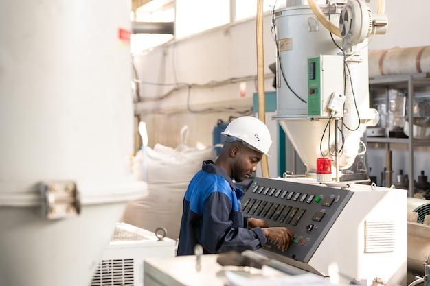 거대한 산업 기계 및 조정 메커니즘의 제어판 앞에 서 있는 작업복과 안전모를 입은 젊은 아프리카 노동자의 측면