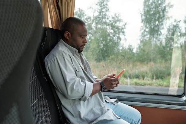 Вид сбоку молодого африканского человека со смартфоном, сидящим у окна