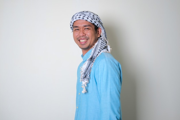 아라비아 셰마그 머리 스카프를 쓴 젊은 아시아 남자의 옆모습은 친근하게 웃고 있다