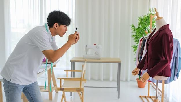 現代のワークショップで作業しながら、スマートフォンを使用してポートフォリオのダミーで流行のジャケットを撮影する若いアジアの仕立て屋の側面図