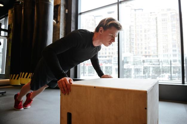 Взгляд со стороны отжиманий молодого атлетического человека на коробке