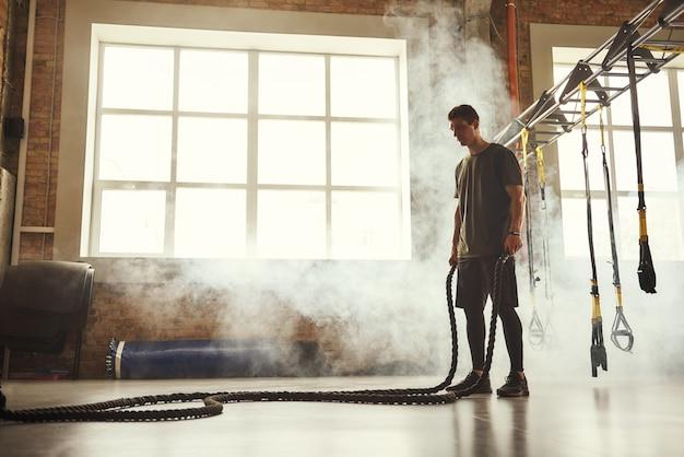 체육관에서 밧줄로 크로스핏 운동을 하는 완벽한 몸을 가진 젊은 운동 남자의 측면