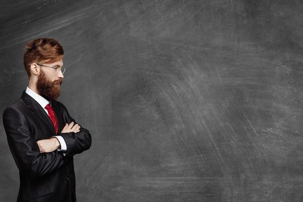 Вид сбоку молодой бородатой брюнетки кавказского бизнесмена в элегантном костюме и очках, стоящего со сложенными руками за доской с задумчивым и задумчивым выражением лица, смотрящего впереди него