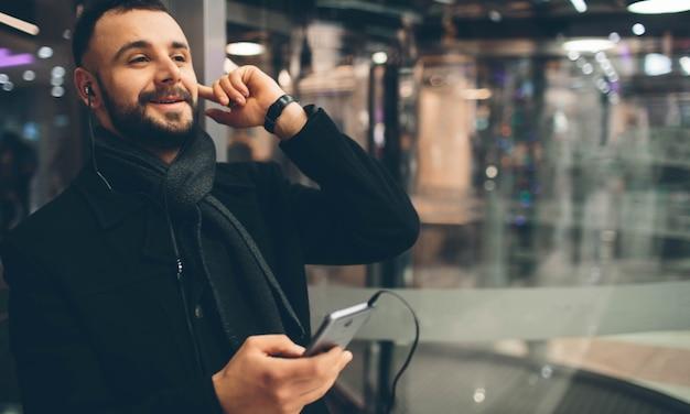 젊은 수염 난 남자의 측면보기, 캐주얼 한 옷을 입고, 그는 거리에 서서 스마트 폰을 사용하고 음악을 듣고 있습니다.