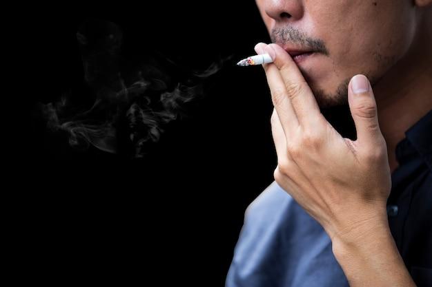 Взгляд со стороны сигареты молодого бородатого человека куря на черной предпосылке.
