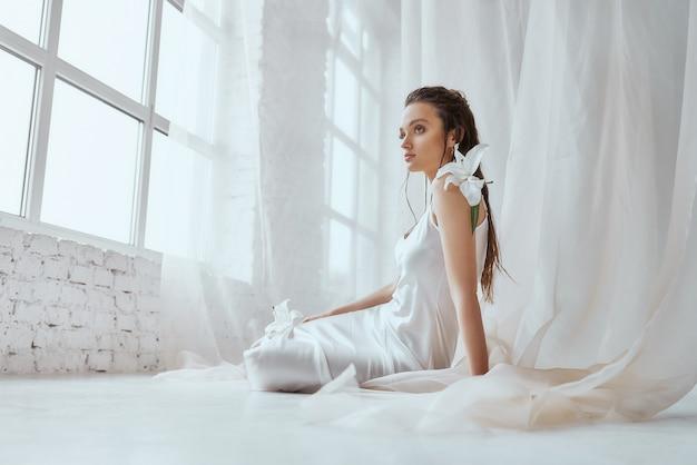 Вид сбоку молодой красивой женщины брюнетки, сидящей на полу и держащей цветок лилии на плече. портрет девушки с мокрыми волосами, позирует на белом фоне и глядя в окно. понятие красоты.