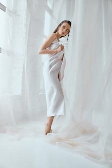 Вид сбоку молодой красивой женщины брюнет стоя и держа цветок лилии. портрет девушки в белом шелковом платье с мокрыми волосами, позирующими на белом фоне между тюлем. понятие красоты.