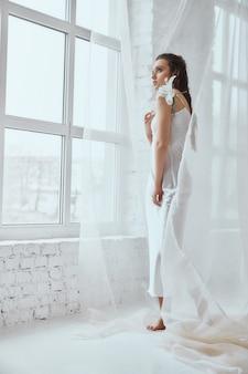 Вид сбоку молодой красивой женщины брюнет стоя и держа цветок лилии. портрет девушки с мокрыми волосами, позирующими на белом фоне и смотрящими в окно между тюлем. понятие красоты.