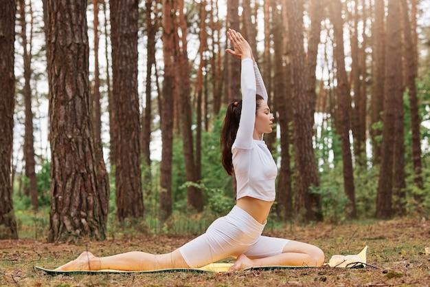 Вид сбоку молодой красивой девушки в белой стильной спортивной одежде, делающей позы йоги в лесу