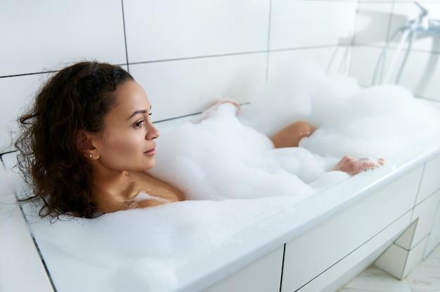 Вид сбоку молодой красивой женщины, лежащей в ванной и принимающей ванну с пеной