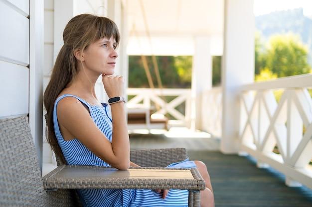 집 현관에 앉아 신선한 공기를 마시며 쉬고 있는 아름다운 젊은 여성의 모습. 좋은 날씨와 함께 자연을 즐기는 개념.