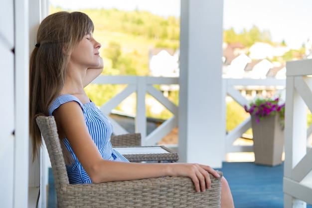 自宅のベランダに座って新鮮な空気で休んでいる若い美しい女性の側面図。