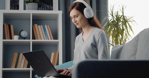 リビングルーム、ローアングルのソファに座っているラップトップとヘッドフォンを使用して若い美しさの側面図