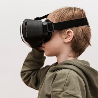 가상 현실 헤드셋을 사용하는 어린 소년의 측면보기