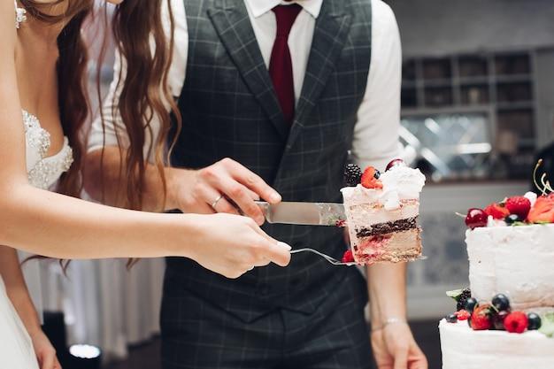 Вид сбоку молодой невесты и жениха, держа нож и тарелку и разрезая вкусный свадебный торт в ресторане. кусок вкусного сладкого десерта. понятие о кондитерских изделиях, празднике и любви.