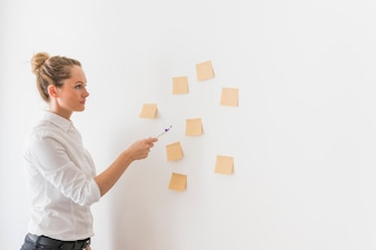 Side view of young business woman pointing toward stick notes on wall