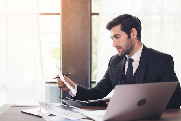 ホームオフィスの机に座ってコンピューターを使用して青年実業家の側面図