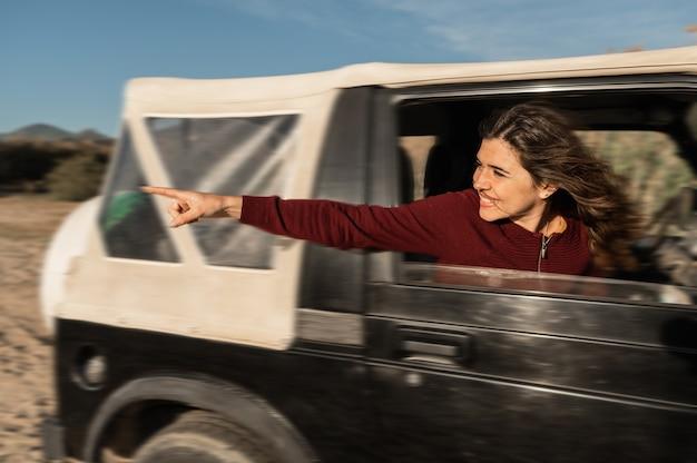 Вид сбоку молодой кавказской счастливой женщины, глядя из окна автомобиля указывая что-то. внедорожник в действии.