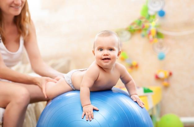 체조 연습을 연습 기저귀를 입고 작은 아기를 돕는 젊은 백인 어머니의 측면보기