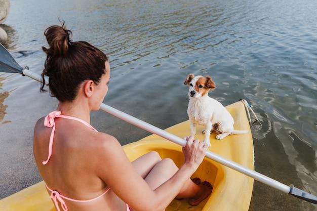Вид сбоку молодой кавказской женщины и собаки джек рассел, сидящей на желтом каноэ в озере в солнечный день. женщина, держащая весло, готова к гребле. лето. домашние животные и природа