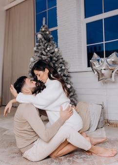 크리스마스 트리 근처에서 포옹하고 순간을 즐기는 젊은 부부의 측면 보기